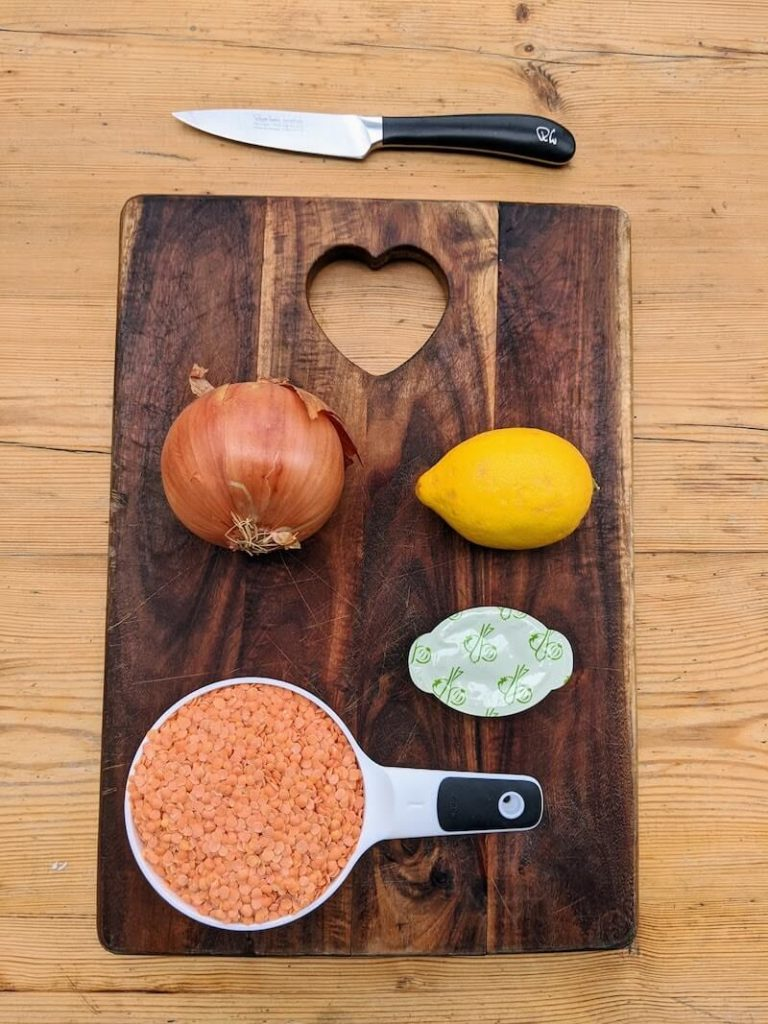 chopping board and knife with onion, lemon, stock cube, lentils
